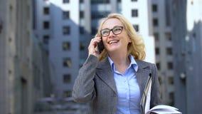 Dame réussie d'affaires avec des documents à disposition parlant le téléphone et souriant, travail clips vidéos