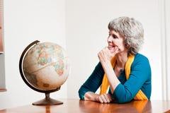 Dame retirée heureuse avec une carte de la terre Photo libre de droits