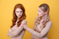 Dame rousse offensée fâchée se tenant près de l'amie blonde de femme Image libre de droits