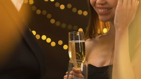 Dame séduisante de sourire tenant le verre avec le champagne et flirtant avec l'homme, partie banque de vidéos