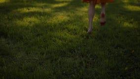 Dame ` s Füße, die durch Gras im Park, barfuß laufen