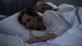 Dame sans sommeil se situant dans le lit tourné de nouveau à la ménopause de douleur de l'homme, santé de femme photographie stock