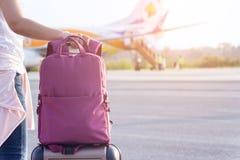 Dame schleppt Gepäck, um eine Fläche fortzufahren, um das w zu reisen stockfoto