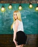 Dame sexy leraar die in korte rok terug terwijl het verklaren van formule kijken Sexy leraarsconcept Vrouw met aardige billen royalty-vrije stock foto