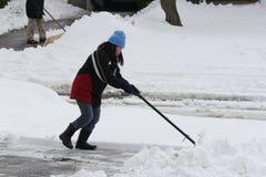 Dame Shoveling Snow van Oprijlaan stock fotografie