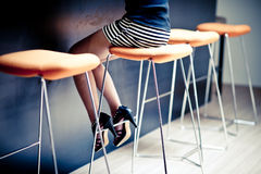 Dame sitzt auf hohen Stühlen stockfotos