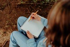 Dame Sketching Outside im Notizbuch lizenzfreie stockfotografie
