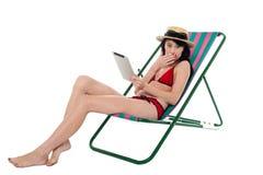 Dame stupéfaite de bikini retenant la tablette Images stock