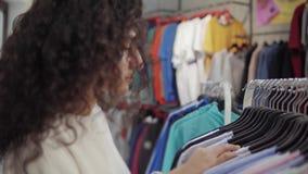 Dame sucht nach einem Sweatshirt auf Gestell in Handelshalle des Geschäftes, bewegliche Aufhänger stock video footage