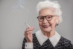 Dame supérieure émotive fumant avec joie Images libres de droits