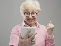Dame supérieure étonnée heureuse utilisant un comprimé numérique image libre de droits