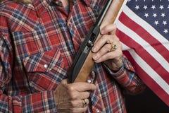Dame supérieure avec le fusil et le drapeau des USA Image libre de droits