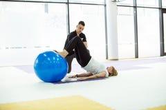 Dame supérieure ayant la séance d'entraînement de boule avec l'entraîneur personnel Images libres de droits
