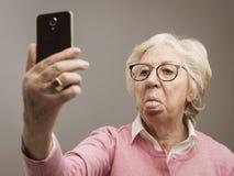 Dame supérieure drôle prenant des selfies avec le toungue  images stock