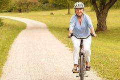 Dame supérieure en bonne santé convenable faisant un cycle  Photos libres de droits