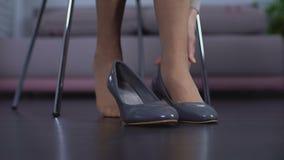 Dame supérieure enlevant de vieilles chaussures, jambes fatiguées, problème de santé de veines variqueuses banque de vidéos