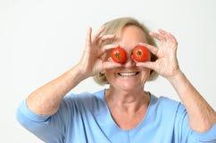 Dame supérieure espiègle tenant des tomates sur ses yeux Photographie stock libre de droits