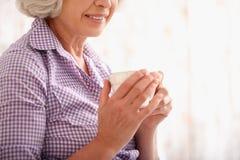 Dame supérieure gaie appréciant la boisson à la maison Photos stock