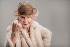 Dame supérieure grincheuse dans le chapeau regardant l'appareil-photo Photo stock