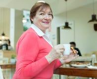 Dame supérieure prenant le petit déjeuner en café Images stock