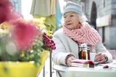 Dame supérieure songeuse détendant en café extérieur Photographie stock libre de droits