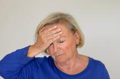 Dame supérieure souffrant avec un mal de tête Photographie stock libre de droits