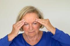 Dame supérieure souffrant avec un mal de tête Images stock