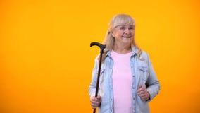 Dame supérieure tenant le bâton de marche, aides d'incapacité pour des personnes âgées, soins de santé photographie stock