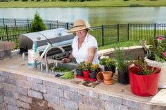 Dame supérieure travaillant dans sa cuisine d'été photo libre de droits