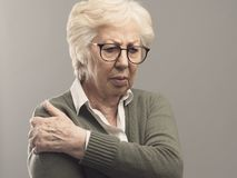 Dame supérieure triste avec le bras et douleurs articulaires images stock
