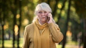 Dame supérieure triste parlant au téléphone portable en parc, seule, aucun famille et amis photographie stock