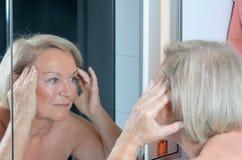 Dame supérieure vérifiant sa peau dans le miroir Photo libre de droits