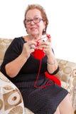 Dame supérieure détendant avec son tricotage Photographie stock libre de droits