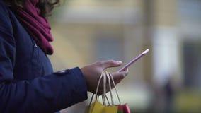 Dame texting vrienden om over kortingen en bevorderingen in opslag te vertellen, het winkelen stock footage