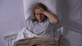 Dame triste se situant dans la douleur de lit de la naus?e et des vertiges de sentiment de grippe intestinale banque de vidéos