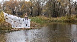 Dame in uitstekende witte kleding in bos door het meer Stock Afbeeldingen