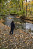 Dame Viewing Fall Scene mit Fluss Stockfotos
