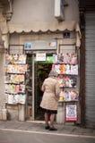 Dame, welche die Zeitschriften herausgestellt im Zeitungskiosk schaut Lizenzfreie Stockbilder