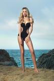 Dame in zwart zwempak op kust Stock Foto