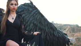 Dame in zwarte lichte kantkleding met zware vleugels en hoornen, vrouwelijke vorm van de duivel, een meisje met een donkere creat stock footage