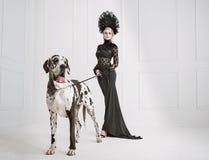 Dame in zwarte met een vriendschappelijke hond royalty-vrije stock afbeeldingen