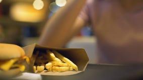 Damehand die Frans-gebraden aardappels van karton op lijst, cholesterolzout nemen stock footage