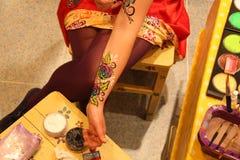 Damekunstenaar van het Kleurrijke Schilderen op een huid of Facepainting met borstel stock afbeeldingen