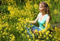 Damen är förlovad i meditation i en stad parkerar bland gula blommor Den härliga kvinnan som gör yogameditation parkerar in arkivfoto