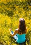 Damen är förlovad i meditation i en stad parkerar bland gula blommor Den härliga kvinnan som gör yogameditation parkerar in royaltyfria foton