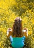 Damen är förlovad i meditation i en stad parkerar bland gula blommor Den härliga kvinnan som gör yogameditation parkerar in royaltyfria bilder