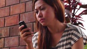 Damen använder mobiltelefonen för att meddela stock video
