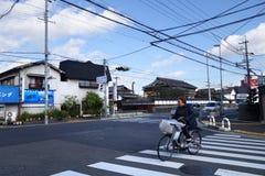 Damen cyklar i vägen i Hiroshima, Japan Arkivbilder