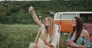 90 Damen der s-Picknickstimmung zwei, welche die selfies sitzen auf den Farbstühlen, Hintergrundgruppe der jungen Freundausgabe n stock footage