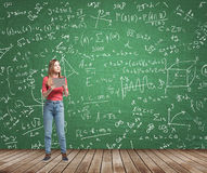 Damen grubblar om invecklat matematikproblem Formler och grafer dras på den gröna svart tavlan Royaltyfria Foton
